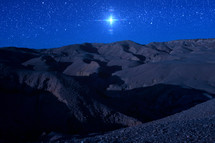 bright star over a desert landscape at night