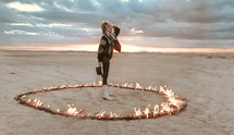 a female standing in a ring of fire in a desert