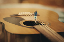 Woman balancing on the strings of a guitar.