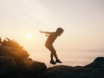 Silhouette of a boy jumping across rocks near the ocean at sunrise.