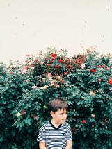 Boy standing outside in front of a rose bush.