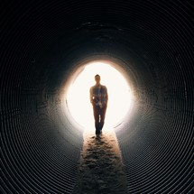 Man walking through dirt in a drainage pipe.