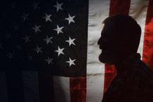 side profile of a bearded man in front of an American flag