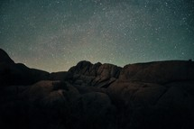 Silhouette of a mountain ridge against a star-lit sky.