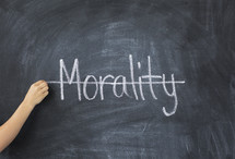 crossing through the word morality off a chalkboard