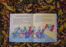 open Children's Bible in fall leaves