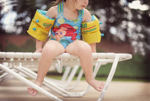 a toddler sitting on a lounge chair at a pool in a swim suit and floaties