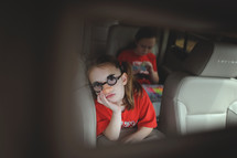 children riding in the backseat of a car
