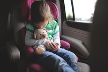 a child in a carseat kissing a teddy bear