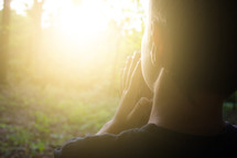 a boy praying outdoors