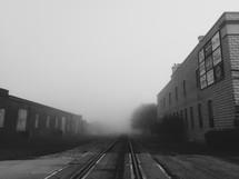 Railroad track between two buildings.