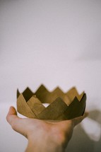 A hand holding a paper crown.