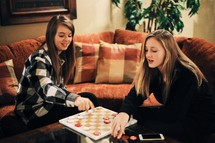 Two young women playing a game of checkers.