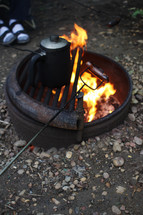 roasting hotdogs over a fire