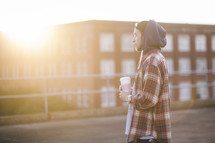 Man in a hoodie standing outside holding a coffee cup at daybreak.