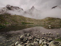 fog and mist in front of mountain peaks nears a stream
