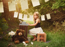 a little girl typing on a typewriter outdoors and pages hanging on a clothesline