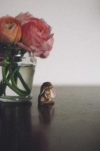 A tiny rabbit figurine sits underneath ranuculus flowers.