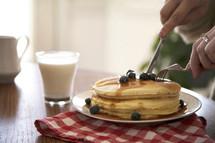 man eating pancakes for breakfast