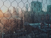 blurry view of a city through chicken wire