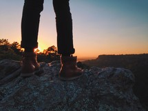 man in boots standing on rock