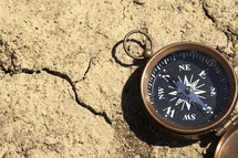 A compass on a parched and cracked ground.