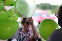 woman with green helium balloons