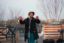 woman singing into a microphone outdoors