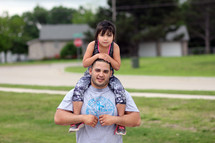 father with daughter on his shoulders standing outdoors