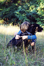 a little boy hugging his dog