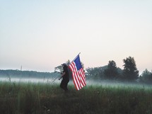 man with an American flag in a field