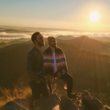 two men standing on top of a mountain under sunlight