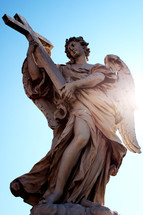 statue of an angel holding a cross