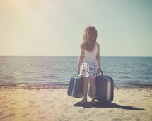 a little girl on a beach holding suitcases