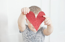 Toddler child holding red paper heart cut out in front of face.