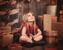 a little girl sitting next to Christmas presents with praying hands