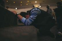 A man kneeling at an altar.