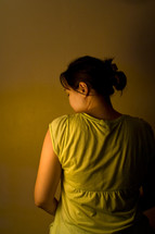 View of woman from behind with partial view of face. Low key image depicting sadness, depression, or loneliness.