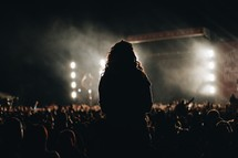 silhouette of a woman standing at a concert