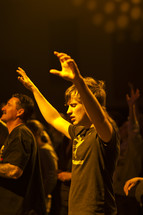 A young man with hands raised in worship.