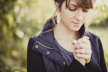 woman with her hands folded in prayer