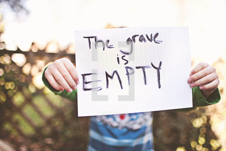 """A child holding up a hand written note that says, """"The grave is empty."""""""