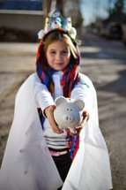 a child dressed as a king holding a piggy bank