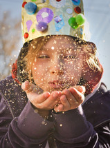 a child dressed as a king blowing glitter