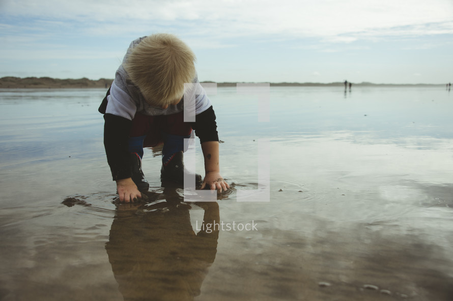 a toddler boy playing in wet sand on a beach