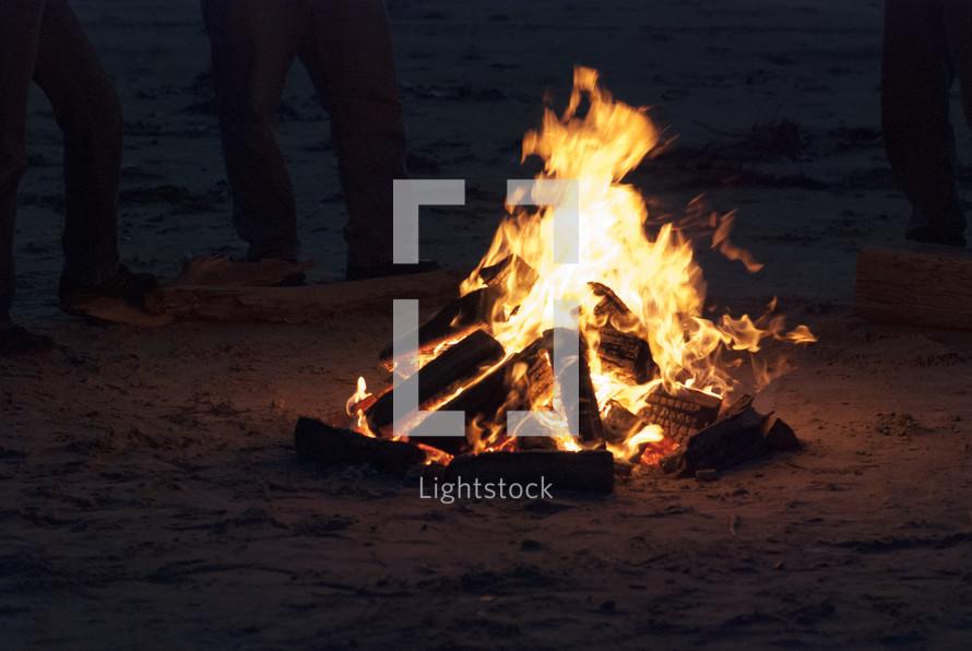 standing around a bonfire on a beach
