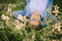 a young man lying in a meadow