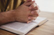 prayer hands on Bible