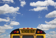 The back of a school bus and a blue sky with clouds.