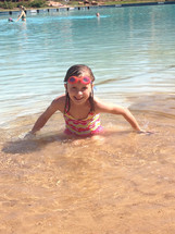 A little girl playing in water on a beach